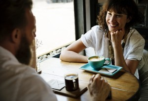A man and a woman enjoying cups of coffee - say goodbye to your neighbors by buying them a cup of java.