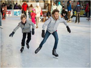 Children ice staking in an outdoor skating rink.