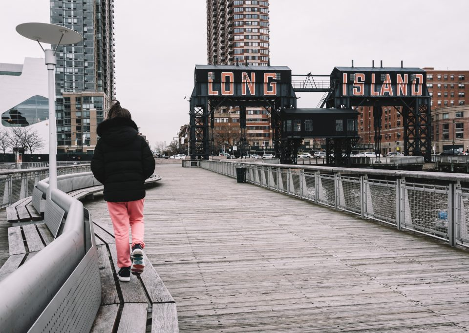 A person walking on a bench, on a bridge in Long Island.