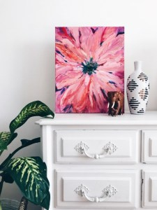 Pink flower painting and a black and white vase on a white antique cuboard with a plant next to them