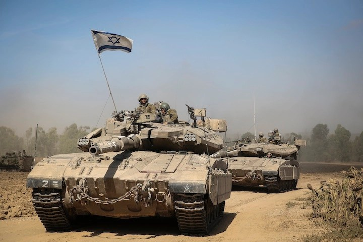 An Israeli tank crossing through a field in southern Israel near the border with Gaza, the day after Israel began its invasion of Gaza, July 18, 2014. (Hadas Parush/Flash 90)