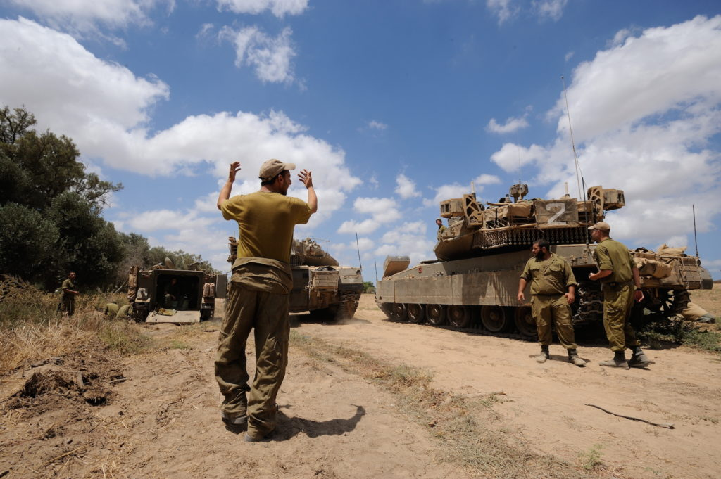An Israeli soldier directing a Merkava tank, at an army deployment area near Israel's border with the Gaza Strip, on July 17, 2014. (Gili Yaari/Flash90)