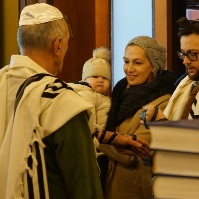 Rabbi Shimon Kutnovsky-Liak, waering glasses, praying with congregants at his synagogues in Jurmala, Latvia on Oct. 30, 2019. (Cnaan Liphshiz)