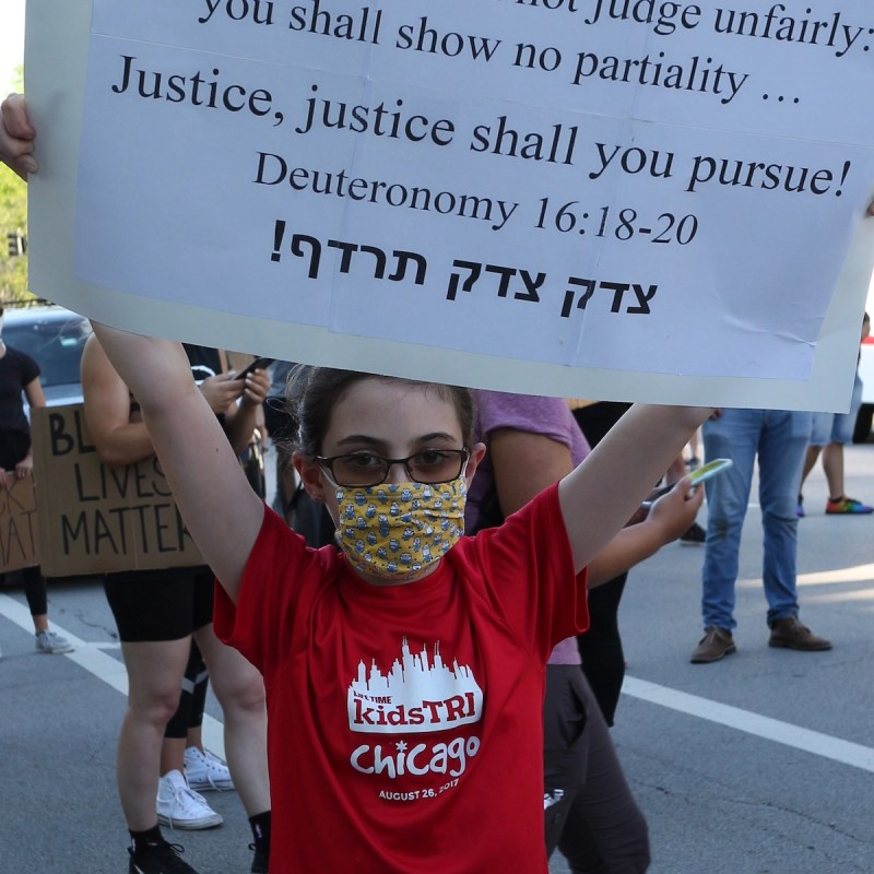 A Jewish demonstrator holds up a sign quoting the Torah in Hebrew. (Ariel Tesher)