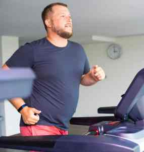 Man in a blue shirt running on a treadmill