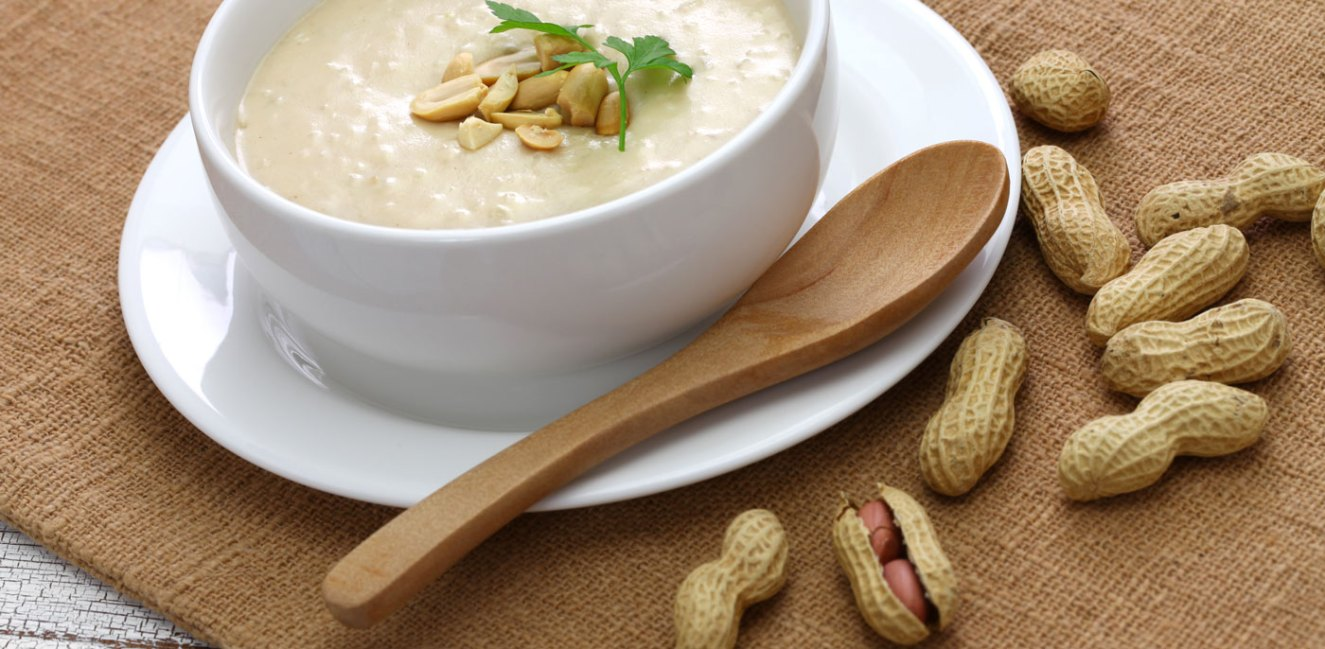 White bowl full of Thai Peanut Soup topped with peanuts.