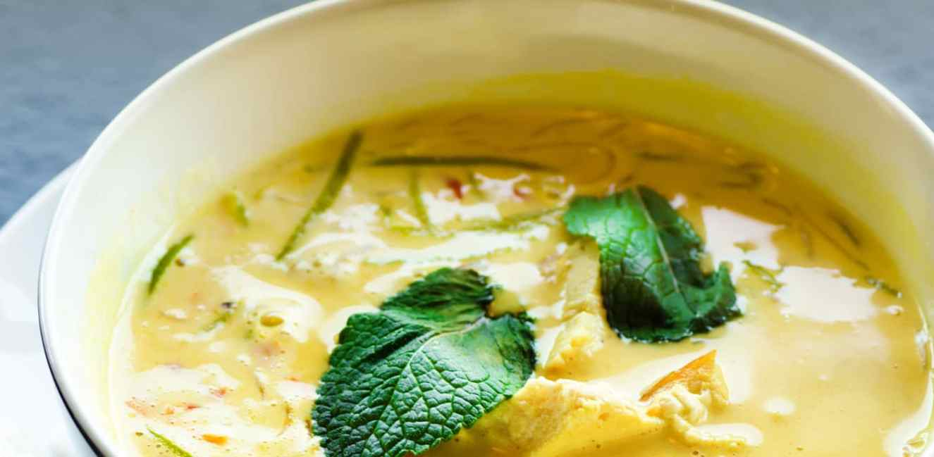 Bowl of curry soup with fresh basil on top