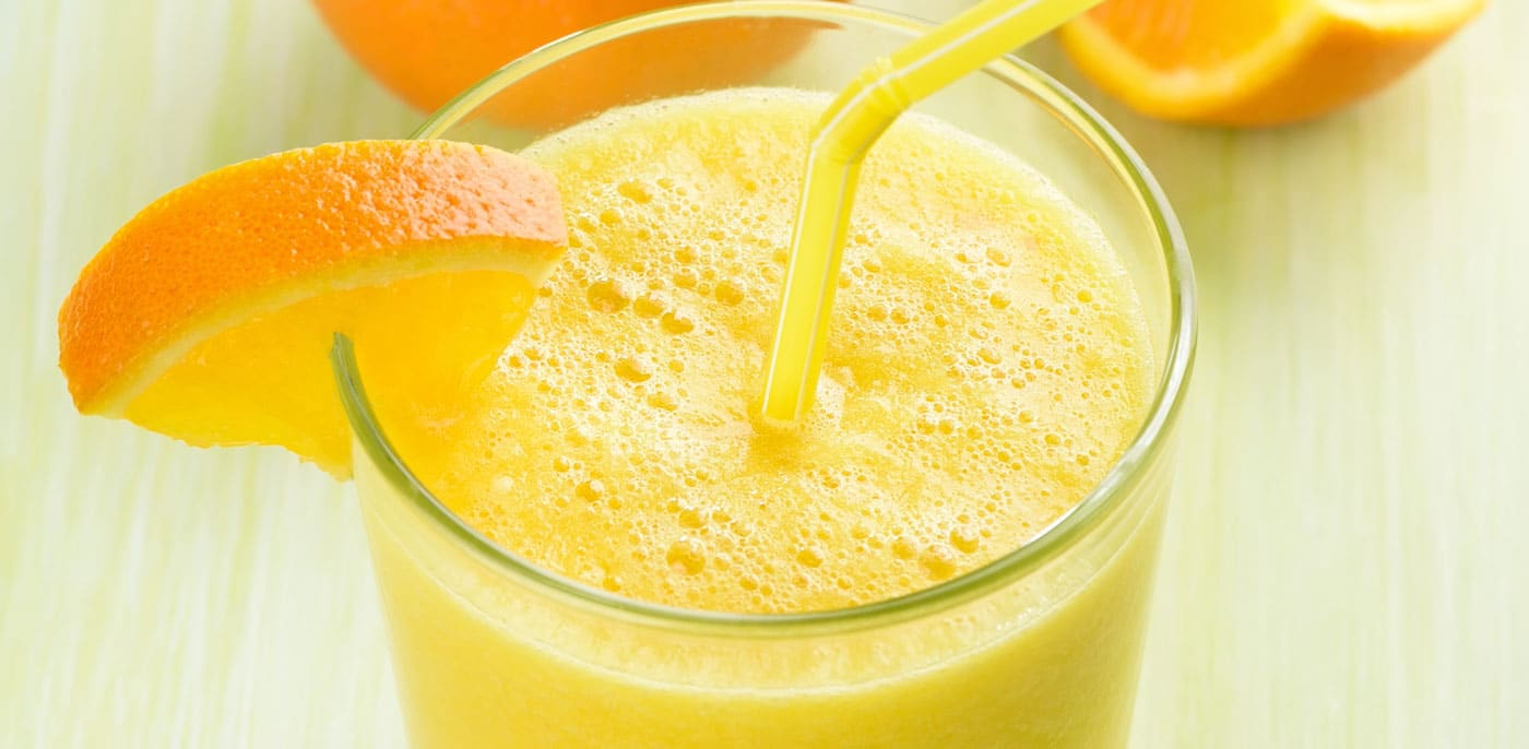 Tall glass of orange juice with an orange wedge of the rim