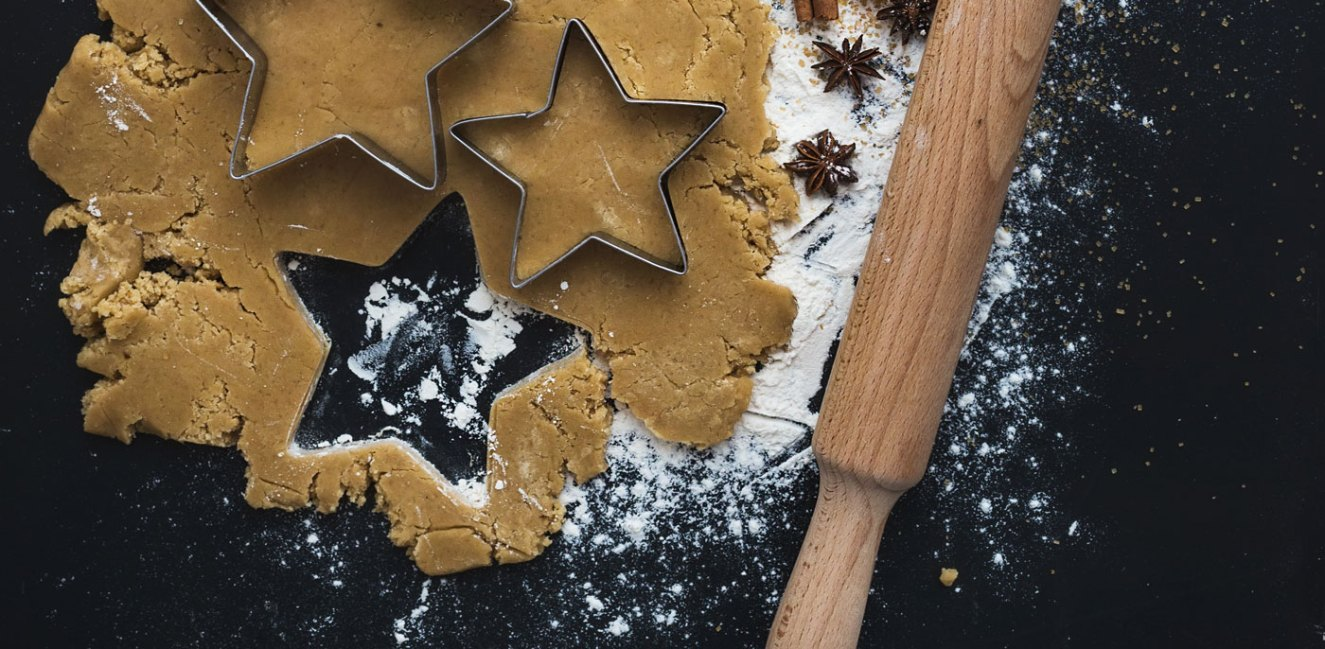Cookie dough being rolled out with rolling pin and star shaped cookie cutter.