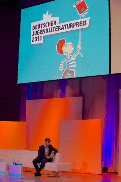 Plakat und Farben der diesjährigen Preisverleihung– unten: Moderator Marc Langebeck // Foto: © Ulf Cronenberg