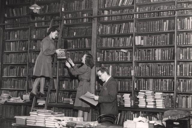 12. Personal bibliotecario recogiendo libros para el préstamo