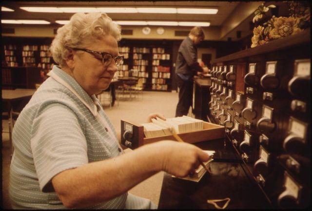 24. Bibliotecaria consultando el catálogo de fichas catalográficas