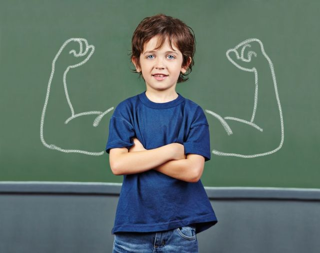 Strong child with muscles drawn on chalkboard in elementary school from Shutterstock