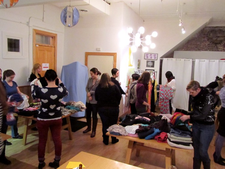 Women browse tables of clothing