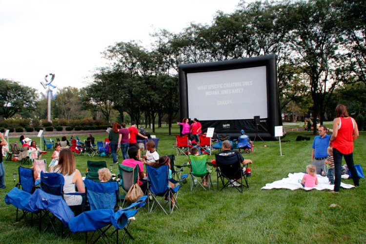 People in lawn chairs in front of movie screen