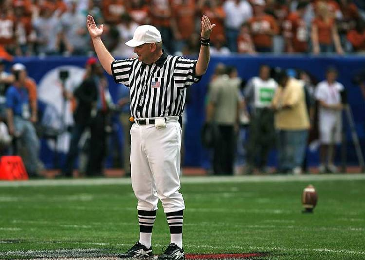 Referee holds up his arms on football field