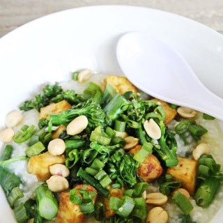 a big bowl of gluten-free and vegan congee with broccoli, scallions, tofu and peanuts