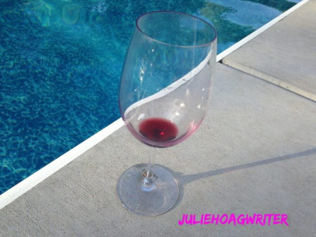 empty wine glass by pool with my logo