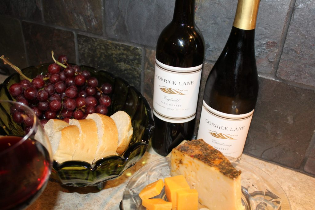 St. Urho's Day and Wine Club Review. Wine bottles of Zinfandel and Chardonnay and 1 glass wine with bread, cheese, grapes