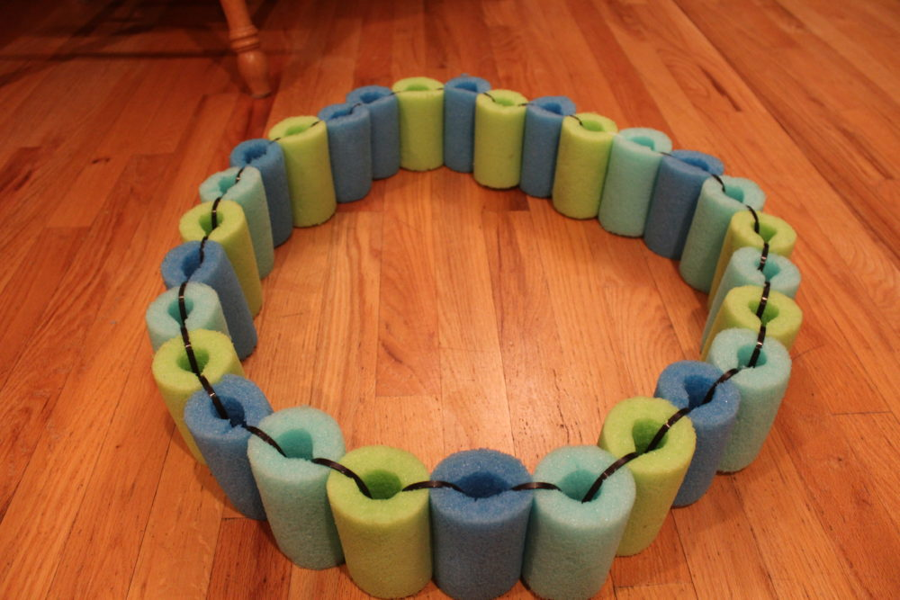 DIY Pool Noodle Float Ring using pieces of noodles strung together to make a float ring raft for kids.