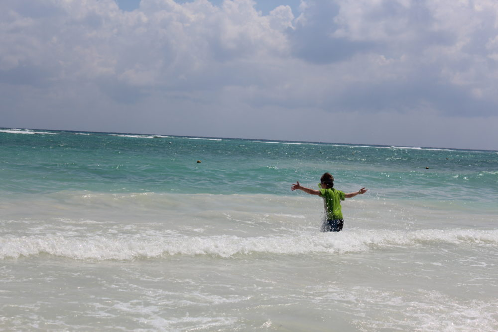 Ocean time! Child swimming in the ocean on a sandy shore at Grand Palladium All-inclusive resort in Riviera Maya, Mexico.