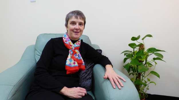 Julie Millar sitting in an armchair in her counselling room. Julie is smiling. Julie is a counsellor in Ellesmere Port and Chester
