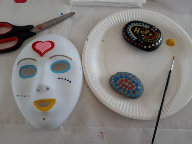 image of a decorated mask, painted stones a paint brush and scisssors, illustrating ways of expressing being creative