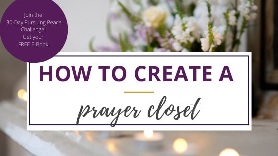 a prayer closet with sprigs of white flowers and lit candles