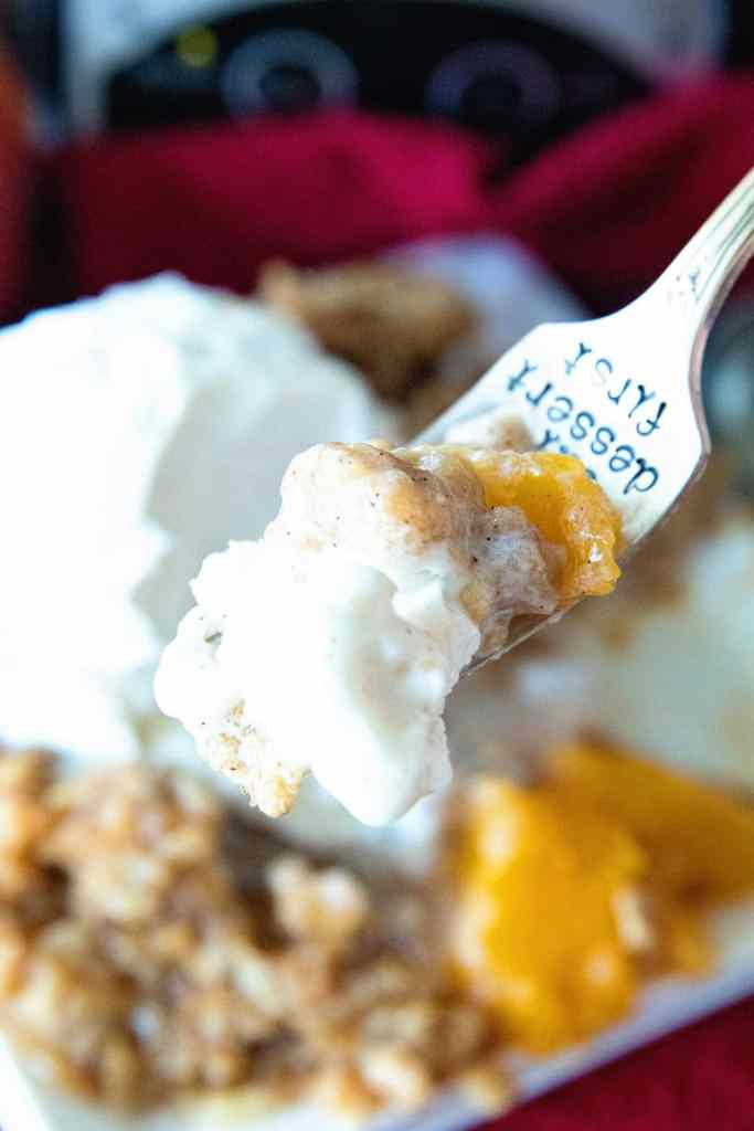 A fork full of Crock Pot Peach Cobbler topped with ice cream.