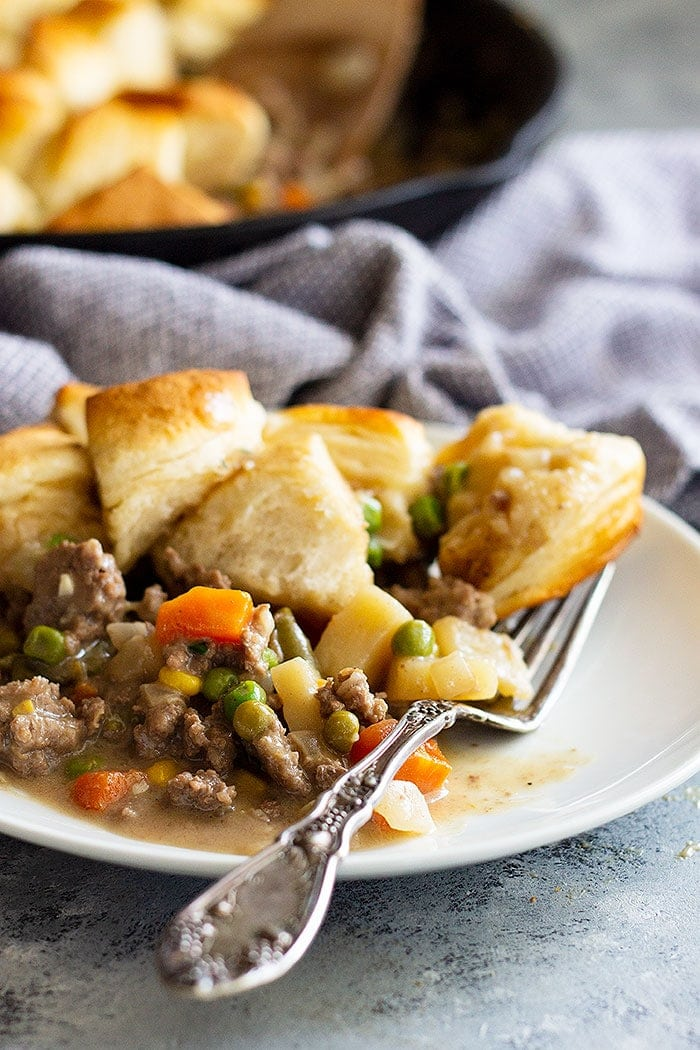 Beef Pot Pie Recipe on a white plate topped with biscuits. A cast iron skillet is in the background filled with more ground beef pot pie.