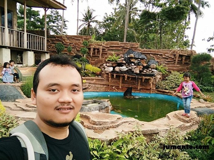 foto kolam ikan dengan kolam renang bukit sakura lampung di belakangnya