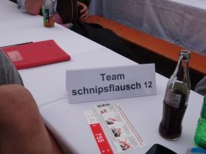 """Hier sieht man ein Bild von einem Tisch beim Heidelberger NCT-Lauf, auf dem Tisch steht das """"Teamschnipsflausch""""-Schild"""