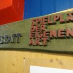 Pinnwand des Unternehmens, ebenfalls mit viel buntem Holz gestaltet
