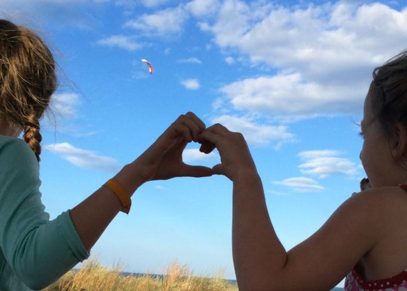 Hier sieht man zwei Kinder, die zusammen mit ihren Händen ein Herz formen, im Hintergrund der blaue Himmel