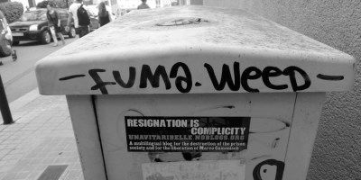 """Hier ist ein Tag (kleiner graffiti-Schriftzug) auf einem Container in Barcelona zu sehen. Die Aufschrift bedeutet übersetzt """"Rauch Marihuana"""""""
