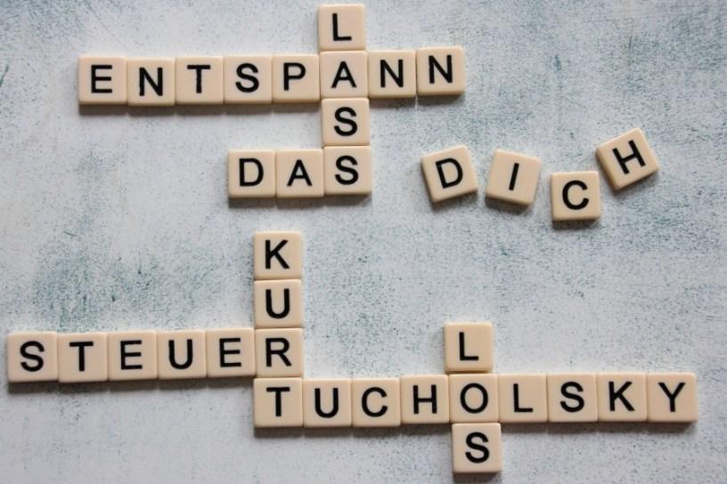 """Hier sind Buchstaben auf einem Tisch zu sehen, die einen Spruch von Kurt Tucholsky bilden: """"Entspann Dich, lass das Steuer los"""""""