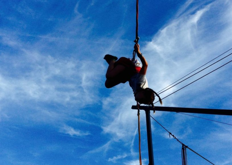 Auf diesem Bild ist ein Mädchen zu sehen, das auf einem Bungee-Trampolin einen Salto schlägt. Im Hintergrund der blaue Himmel. Da wir ganz unter uns sind: Das sportliche Kind dort ist meines, und ich freue mich so sehr darüber, ich kann es gar nicht sagen.
