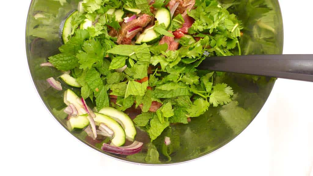 An easy Thai recipe: chilled Thai beef salad with cucumber, tomatoes, mint, cilantro and red onion in a spicy fish sauce and lemon marinade!