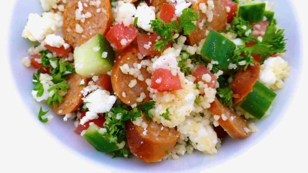 Here's my savory couscous salad with crispy baked merguez sausages, freshly diced cucumber, tomato and feta cheese! Great healthy lunch salad!