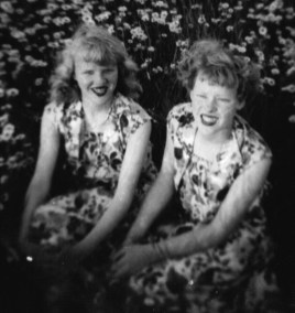 Helen Rose and Shirley sitting among daisies, 1950