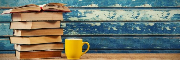 How to sell books on Amazon: stack of books and a yellow mug in front of a wall