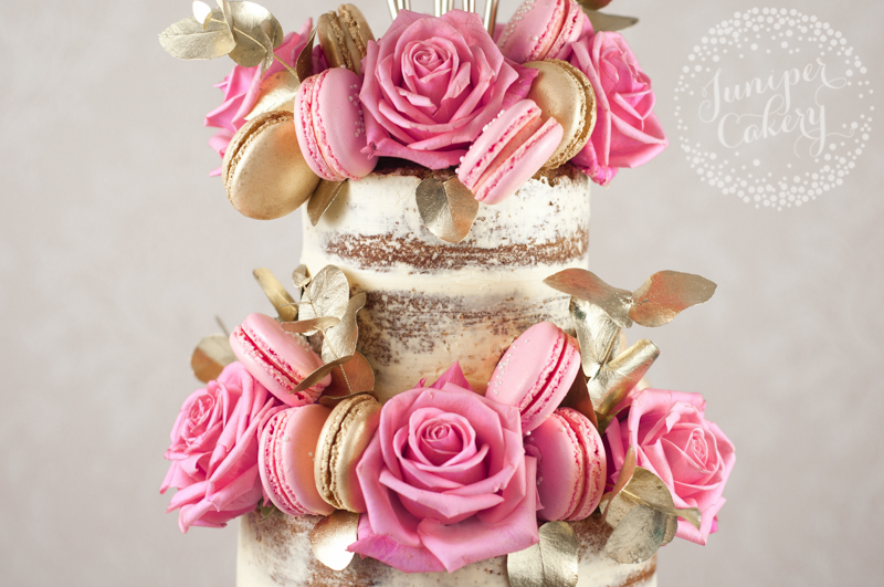 Pink and gold naked cake covered with roses and macarons by Juniper Cakery