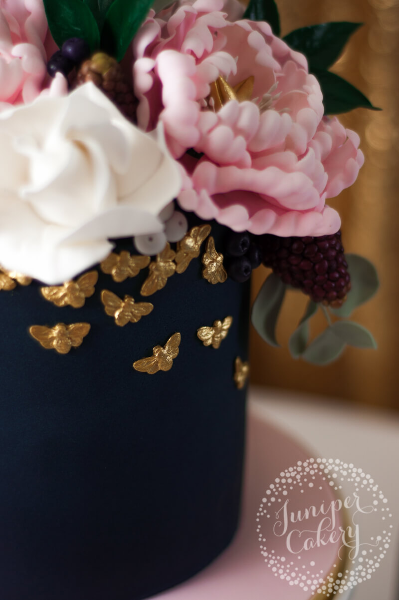Navy and blush floral peony cake with gold bees by Juniper Cakery