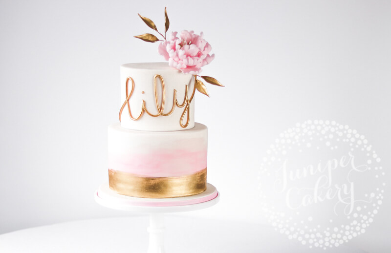 Pretty blush pink wash cake with gold accents by Juniper Cakery