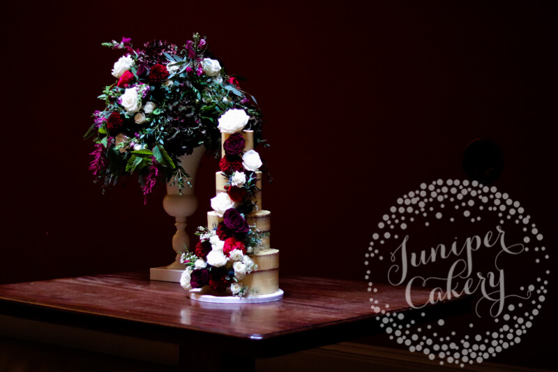 Burgundy themed semi-naked wedding cake at Rise Hall by Juniper Cakery