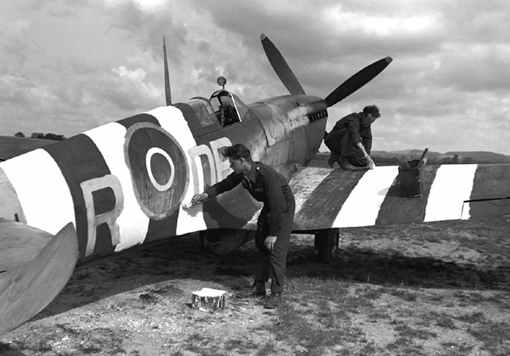 Stan Rivers and Ken Allenby, No. 411 Squadron, painting D-Day colours on a Spitfire. Special white markings were painted on the fuselage and wings of all Allied aircraft in preparation for D-Day.