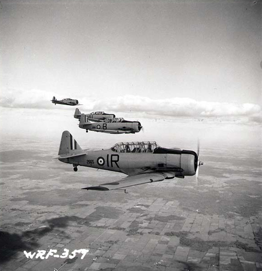 Quatre North American Harvard volent en formation près de l'École de pilotage militaire no 2 à Ottawa, en juillet 1941.