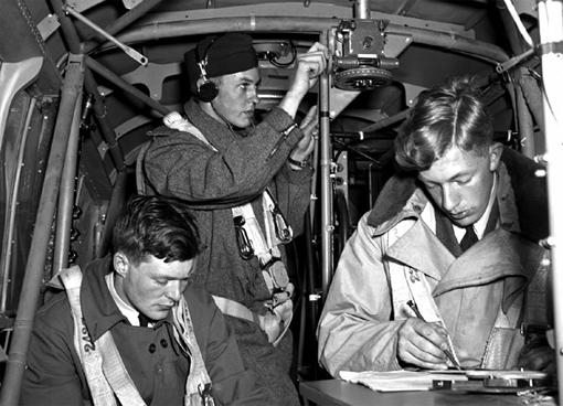 Les sergents E.M. Romilly, ARC, W.H. Betts, RAAF, et J.A. Mahoud, RAF, mettent en application les techniques de navigation à bord d'un Anson de l'École de navigation aérienne no 1 de Rivers au Manitoba, le 4 juin 1941.