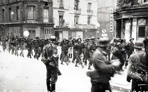 Des prisonniers canadiens sont escortés par des gardes allemands à travers les rues de Dieppe, le 19 août 1942.