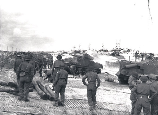 1st Hussars tanks and men of the 7th Infantry Brigade landing on a crowded beach at Courseulles-sur-Mer, June 6th,1944.